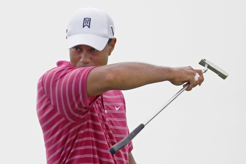 Woods wipes his face with his sleeve on the 12th green during practice round for the 92nd PGA Golf Championship in Haven