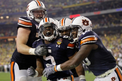 Auburn Tigers' Michael Dyer celebrates with teammates Brandon Mosley and Kodi Burns after a run to the half yard line against the Oregon Ducks in the fourth quarter in the NCAA BCS National Championship college football game in Glendale