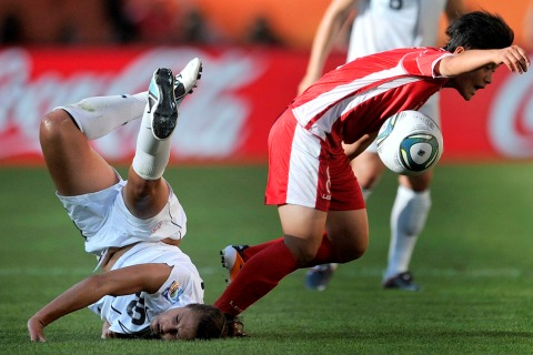 USA's midfielder Carli Lloyd (L) and North Korea's midfielder Kim Su Gyong, vie for the ball