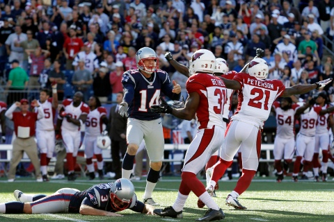 New England Patriots kicker Gostkowski lays on the ground after missing a field goal as punter Mesko reacts while Arizona Cardinals players celebrate their win during the final second of the fourth quarter of their NFL football game in Foxborough