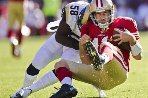 image: San Francisco 49ers quarterback Alex Smith is tackled by St. Louis Rams' Jo-Lonn Dunbar during their game at Candlestick Park in San Francisco, Nov. 11, 2012.