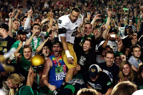 image: Fans celebrate with Notre Dame wide receiver Chris Brown after they defeated USC during their NCAA college football game at the Coliseum in Los Angeles, Nov. 24, 2012.