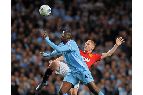 Manchester City's Ivory Coast footballer Yaya Toure (Foreground) vies for the ball against Manchester United's English midfielder Paul Scholes