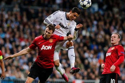 Real Madrid's Portuguese forward Cristiano Ronaldo vies with Manchester United's Northern Irish defender Jonny Evans during the UEFA Champions League round of 16 first leg football match Real Madrid CF vs Manchester United FC at the Santiago Bernabeu stadium in Madrid on Feb. 13, 2013.