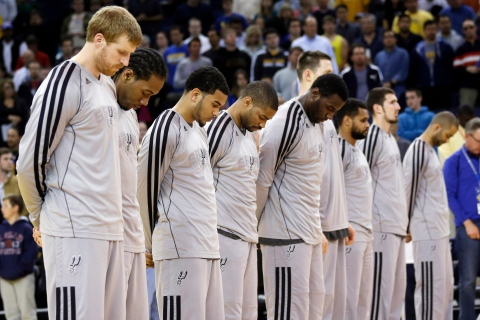 Members of the San Antonio Spurs observe a moment of silence for victims of the Boston Marathon explosions before an NBA basketball game against the Golden State Warriors in Oakland, Calif., April 15, 2013.