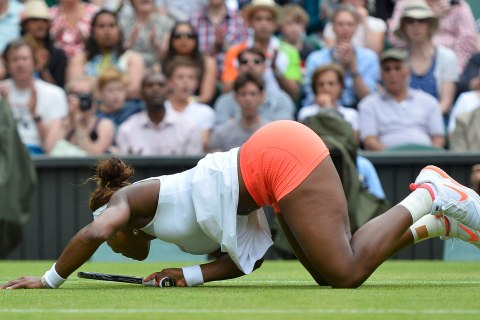 Serena Williams of the U.S. falls after diving for a shot during her women's singles tennis match against Sabine Lisicki of Germany at the Wimbledon Tennis Championships, in London