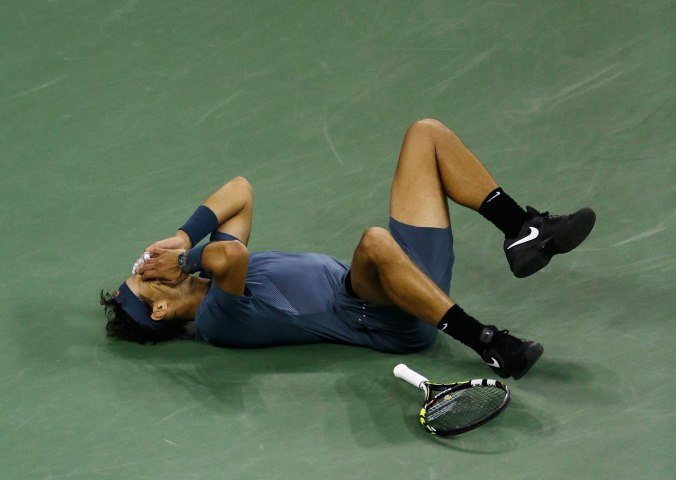 Rafael Nadal, of Spain, falls to the court after defeating Novak Djokovic, of Serbia, during the men's singles final of the 2013 U.S. Open tennis tournament, Sept. 9, 2013, in New York.