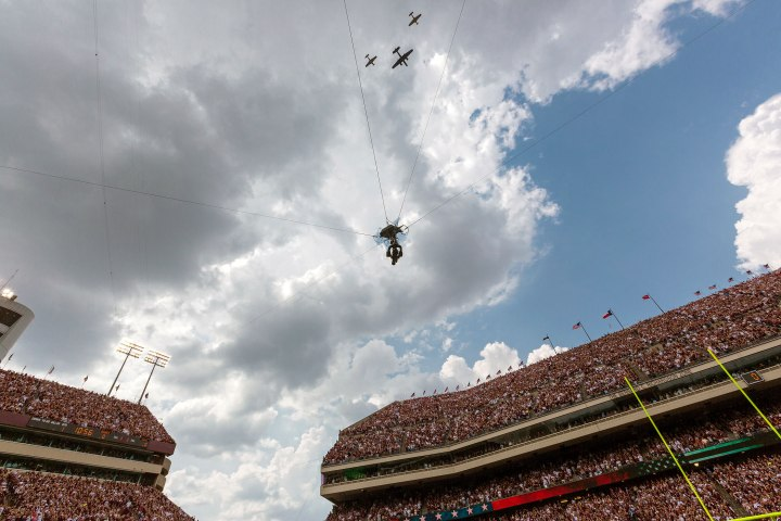 A trio of bombers and a television camera fly over Kyle Field.