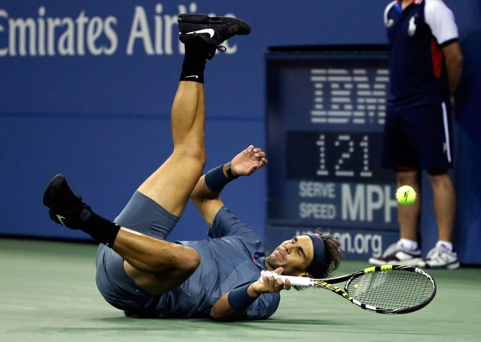 Rafael Nadal, of Spain, falls to the court as he misses a shot to Novak Djokovic, of Serbia, during the men's singles final of the 2013 U.S. Open tennis tournament, Sept. 9, 2013, in New York.