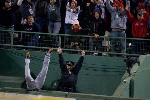 Detroit's Torii Hunter falls into the bullpen trying to catch Red Sox designated hitter David Ortiz's home run that tied the game in the eighth inning of game two of the American League Championship Series at Fenway Park in Boston, Oct. 13, 2013.