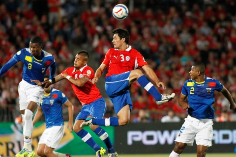 Chile's Gonzalez heads the ball between Ecuador's Guagua and Erazo during their 2014 World Cup qualifying soccer match in Santiago