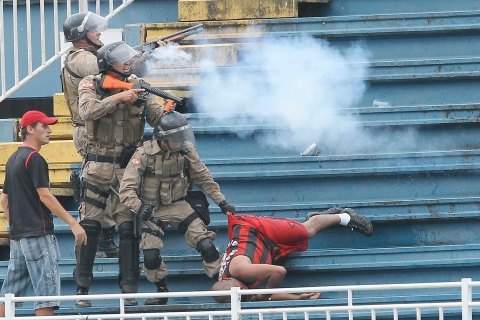 Policemen fire rubber bullets as they help an Atletico Paranaense fan in Joinville