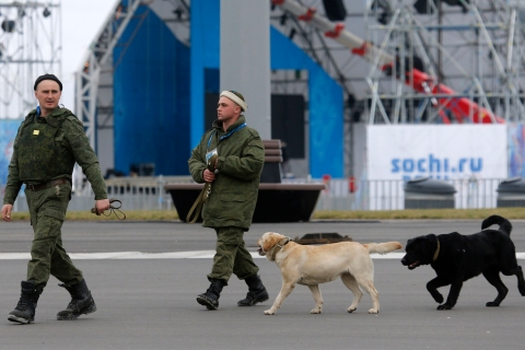 Members of Russian military patrol with sniffer dogs inside the Olympic Park in the Adler district of Sochi