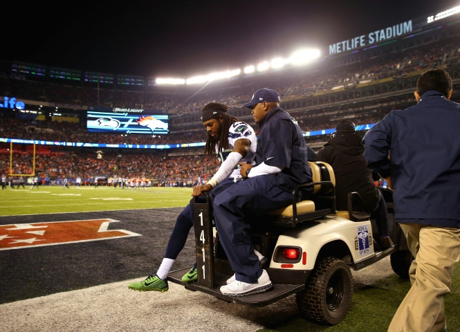 Cornerback Richard Sherman of the Seattle Seahawks is helped off the field during the fourth quarter.