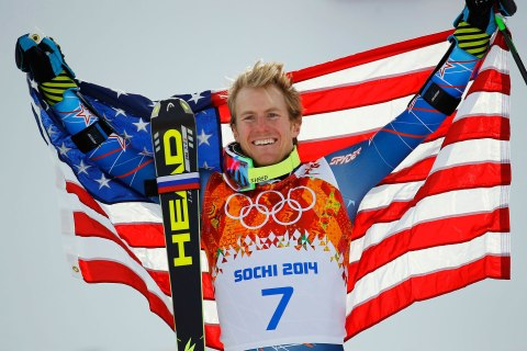 Winner Ted Ligety of the U.S. holds up his national flag during the flower ceremony for the men's alpine skiing giant slalom event in the Sochi 2014 Winter Olympics at the Rosa Khutor Alpine Center